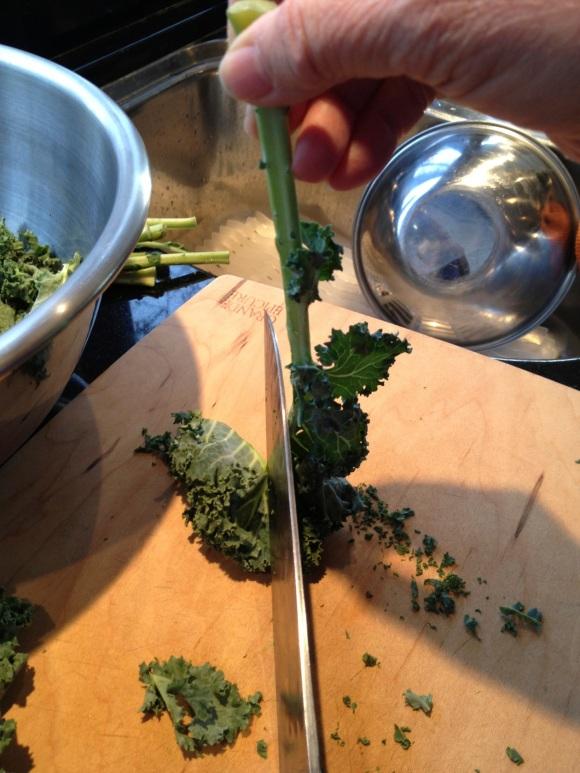 slicing leaves from kale stem