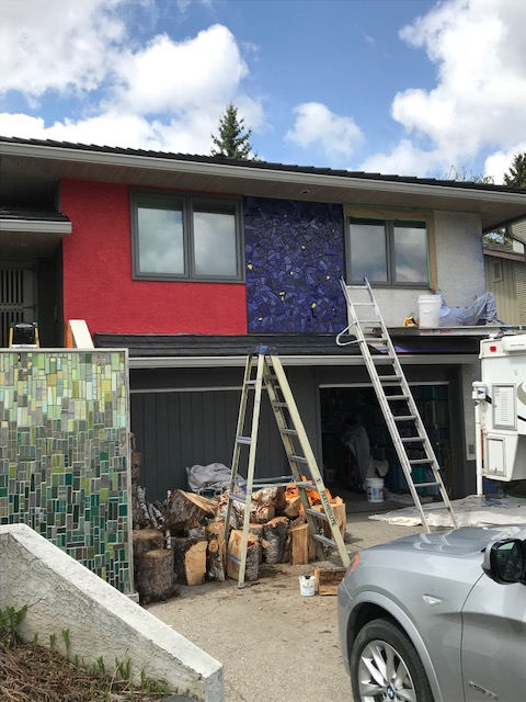house during painting showing tile mosaics and stucco