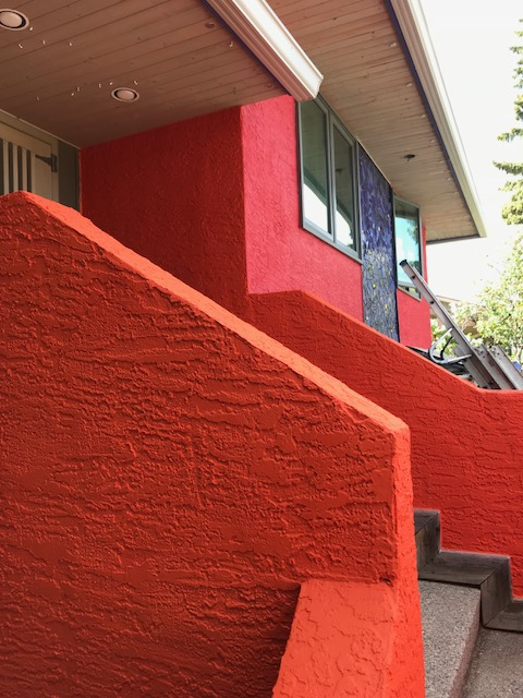 orange and coral stucco with blue tile mosaic